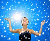 people, happiness, holidays and christmas concept - smiling woman raising hands and looking up over blue snowy background