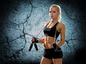 sport, fitness, training, stamina and people concept - young sporty woman with jumping rope over concrete wall background