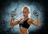 sport, fitness, training, weightlifting and people concept - young sporty woman with dumbbells flexing biceps over concrete wall background