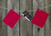 Blank red Christmas cards and green plaid heart hanging on clothesline