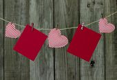 Red holiday cards and red and white striped hearts hanging on clothesline