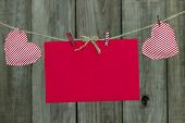 Red holiday card envelope and hearts hanging on clothesline with wooden background