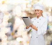 cooking, holidays, technology and people concept - smiling female chef, cook or baker with tablet pc computer over lights background