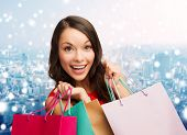 sale, gifts, christmas, holidays and people concept - smiling woman with colorful shopping bags over snowy city background