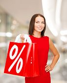 people, gifts, christmas and holidays concept - smiling young woman in red dress holding shopping bags with percent and sale sign over mall background