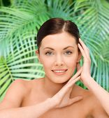 beauty, people and health concept - smiling young woman with bare shoulders over palm tree leaves background