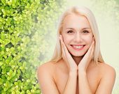 beauty, people and ecology concept - beautiful young woman touching her face skin over green background
