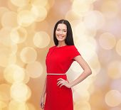 christmas, holidays, valentine's day, celebration and people concept - smiling woman in red dress over beige lights background