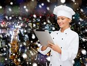 cooking, holidays, technology and people concept - smiling female chef, cook or baker with tablet pc computer over snowy night city background