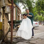 HANOI, VIETNAM - APRIL 8: Unidentified barber cut hair on street on April 8, 2014 in Hanoi, Vietnam. Barber who doesn't have a shop have to work on street.