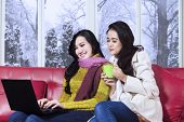 Two Girl In Winter Clothes Using Laptop