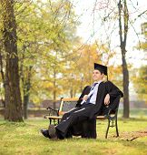Graduate student holding diploma seated on bench in park shot with tilt and shift lens