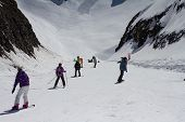 Skiers and snowboarders going down the slope at ski resort. Krasnaya Polyana, Sochi, Russia