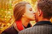 Young Woman Kissing A Man In Autumn Park