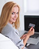 Woman shopping online with credit card and computer.