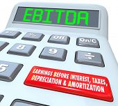 EBITDA word in digital letters on a calculator display to illustrate earnings before interest, taxes, depreciation and amortization