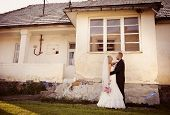 Bride and groom by the old house
