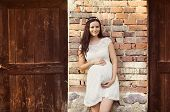 Pregnant woman against brick wall