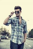 Trendy Young Man Standing Outside Smoking, Lowering Sunglasses