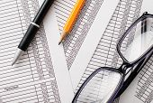Eyeglasses, Pen And Pencil On Business Reports