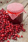 Jar Of Jam And Fresh Red Cranberries On Wooden Table.