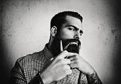 B/w Portrait Of A Man Grooming His Beard With Scissors