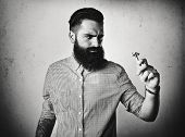 B/w Portrait Of A Brutal Bearded Man Looking At Vintage Shaver