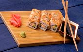 picture of blue crab  - Delicious Salmon Maki Roll with Crab Cucumber Sesame Seeds and Soy Sauce Ginger Chop Sticks and Wasabi closeup on Straw Mat on Dark Blue Wooden background - JPG