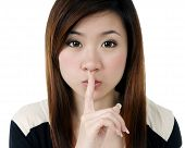 Attractive young woman with a finger over her lips