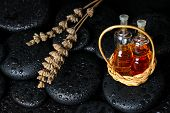 Aromatic Spa Concept Of Bottles Essential Oil In Basket And Dried Lavenders On Black Zen Basalt Ston