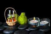 Aromatic Spa Concept Of Bergamot Fruits, Candles And Bottles Essential Oil In Basket On Zen Black St