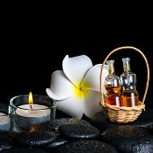 Aromatic Spa Setting Of Plumeria Flower, Candles And Bottles Essential Oil On Zen Stones, Closeup