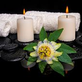 Spa Still Life Of Passiflora Flower, Green Leaf With Drop, Towels And Candles On Zen Stones In Refle