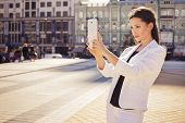 Beautiful Brunette Business Woman In White Suit Photographing On A Tablet In Her Hands Outdoors. Cop