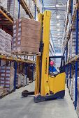 Yellow Pedestrian Stacker Lifts Pallet With Boxes On The Shelves.