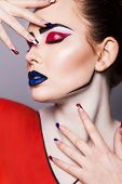 Beautiful brunette woman with creative pop art make up and geometric nail style black lines and clos