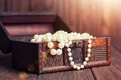 picture of treasure chest  - old treasure chest with pearl necklaces standing on wooden table - JPG