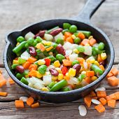 stock photo of lenten  - Mixed vegetable meal in old frying pan closeup and ingredients on wooden table - JPG