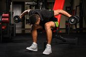 picture of bent over  - Young man doing Seated Bent Over Dumbbell Reverse Fly workout in gym - JPG