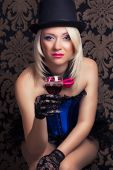 image of cabaret  - beautiful cabaret woman with a glass of red wine posing on chair - JPG