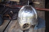 stock photo of viking  - Replica of Viking helmet with visible stroke marks on wooden table in front of hauberk and sword - JPG
