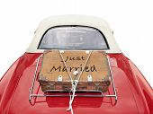 image of married  - Just Married written on a suitcase placed on the trunk of a red car isolated with clipping path - JPG