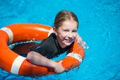 foto of lifeline  - happy little girl swims in a wetsuit with a lifeline in the pool - JPG