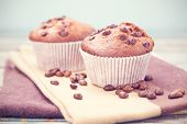 picture of chocolate muffin  - two fresh chocolate muffins and grains of coffee in a studio - JPG
