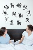 stock photo of horoscope signs  - Man and surprised woman in bedroom surrounded looking up at horoscope zodiac 12 signs - JPG