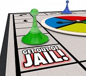 picture of jail  - Get Out of Jail words on a board game and player piece moving to illustrate escaping from prisoner after arrest and court - JPG