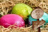 picture of laying eggs  - Easter egg hunt sign against three colouful easter eggs nestled in straw nest - JPG