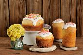 picture of easter candy  - Paska East European easter sweet breads decorated with icing and candied fruits with yellow flowers on wooden background with space - JPG
