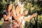 foto of swing  - Two young women playing with swing in a park  - JPG