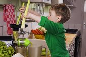 stock photo of juicer  - Little boy making green juice with a slow juicer - JPG